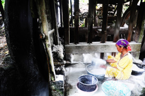 a woman making rice powder during a hazy morning in nagari batu kalang west sumatra indonesia